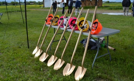 Shovels with construction hats leaning against a table