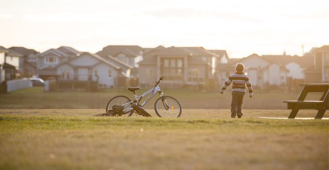 Child and bike in park at sunset
